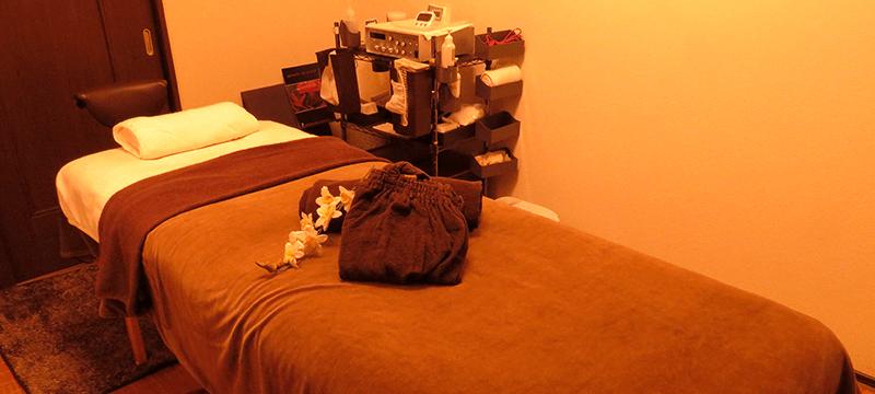 ガウンが置かれたベッドのある施術室
